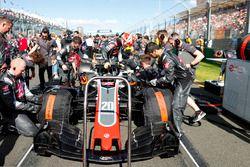 Haas F1 engineers prepareren de wagen van Kevin Magnussen, Haas F1 Team VF-18 Ferrari, op de grid