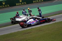 Гонщик Scuderia Toro Rosso Пьер Гасли проезжает мимо остановившейся Williams FW40 Лэнса Стролла