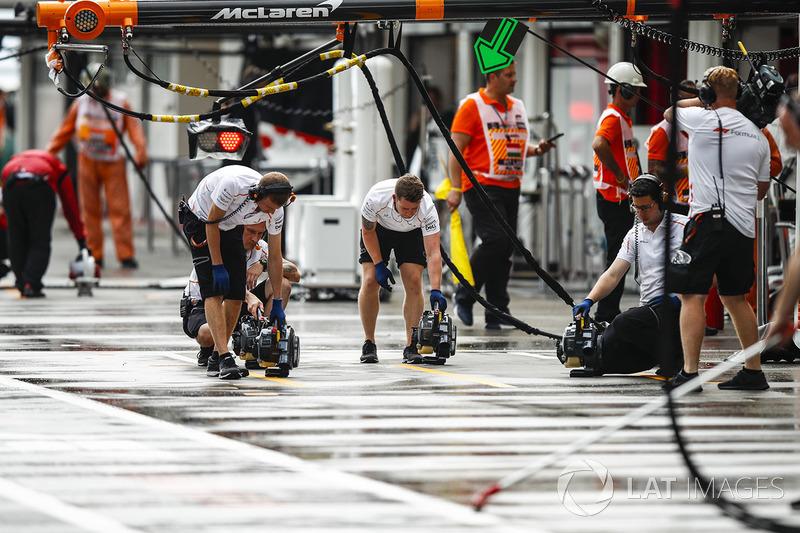 Mecánicos de McLaren secando el suelo