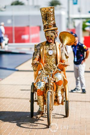A somewhat decorated chap rides a tricycle in the paddock