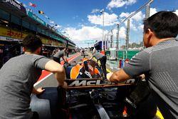 Mecánicos de McLaren empujaN el coche de Fernando Alonso, McLaren MCL32, en el pit lane