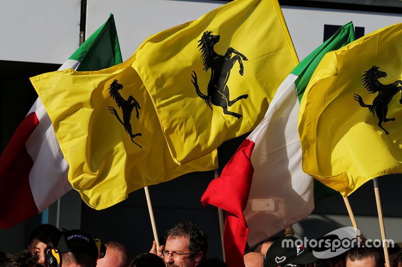 Ferrari festeggia con le bandiere sotto al podio