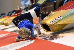A young fans examines the front of a Gold Leaf Lotus 49 at close quarters
