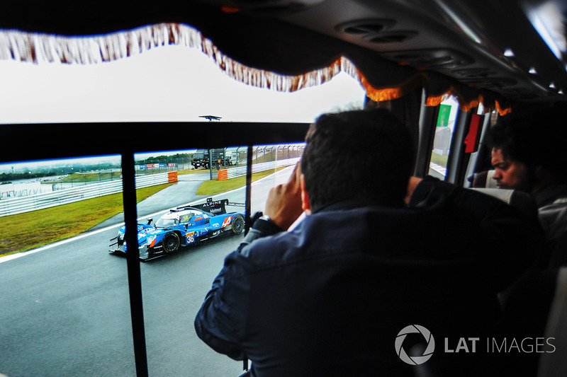 السياح في الباص يستمتعون بمنظر الحلبة والسيارات