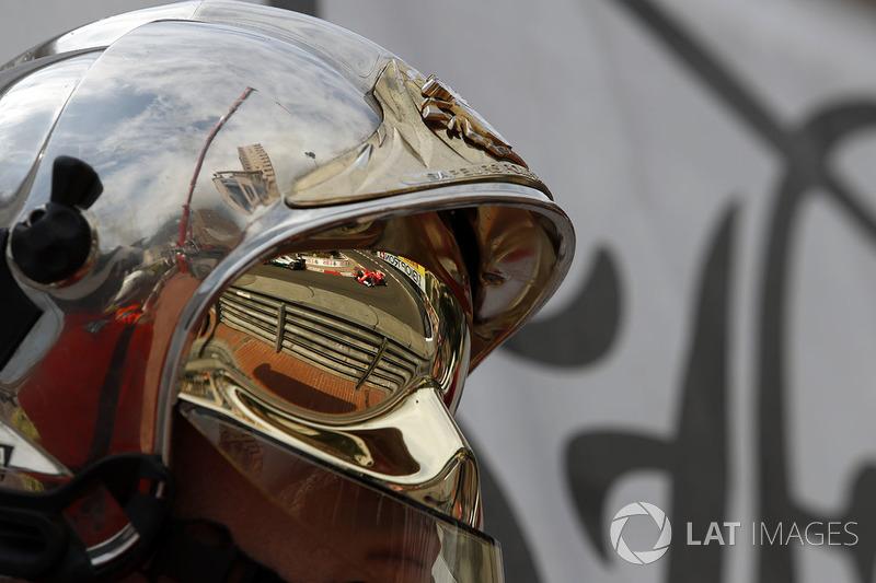 Kimi Räikkönen, Ferrari SF70-H, als Reflexion im Helm eines Feuerwehrmanns