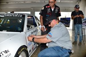 Herbert Gomez helps Trans-Am announcer The Gorilla apply the original 1988 SCCA Runoffs tech-inspection sticker to the restored 1988 Acura Integra.
