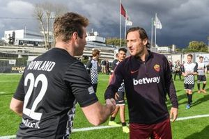Roma player Francesco Totti shakes hands with Oliver Rowland, Nissan e.Dams