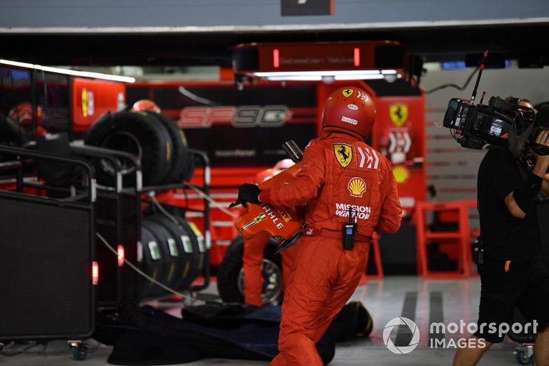 Un membro della pit crew Ferrari con il musetto danneggiato della monoposto di Sebastian Vettel, Ferrari SF90