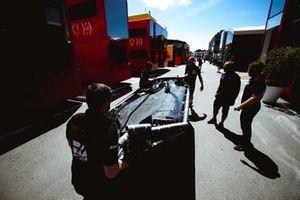 Механики Haas F1 Team несут днище болида по паддоку