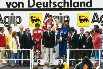 Second placed Alain Prost, McLaren, race winner Michele Alboreto, Ferra and third placed Jacques Laffite, Ligier celebrate on the podium