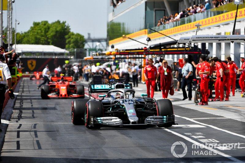 Lewis Hamilton, Mercedes AMG F1 W10, leads Charles Leclerc, Ferrari SF90, in the pit lane