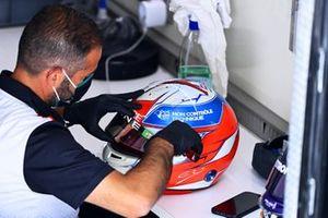 A Bell technician works on the helmet of Esteban Ocon, Alpine F1