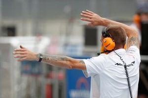 A McLaren mechanic gives direction