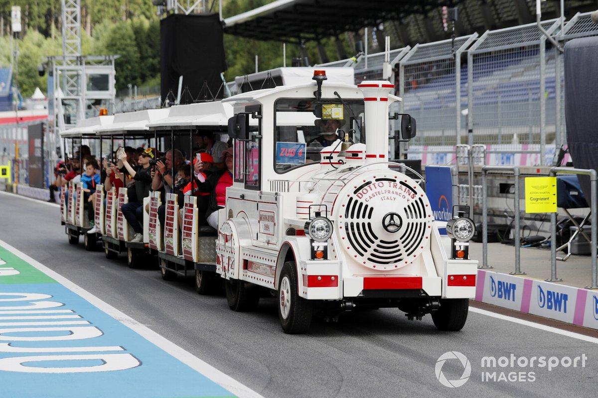 Los aficionados viajan en un tren terrestre por el pitlane