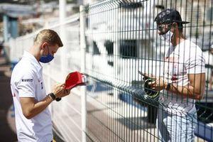 Mick Schumacher, Haas F1, signs a hat for a fan