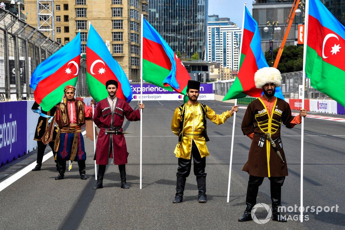 Artistas con trajes tradicionales con banderas de Azerbaiyán en la parrilla