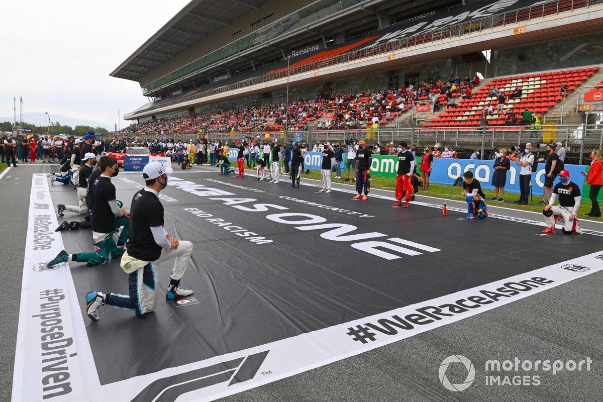 Los pilotos se ponen de pie y se arrodillan en la parrilla de salida en apoyo de la campaña We race as one
