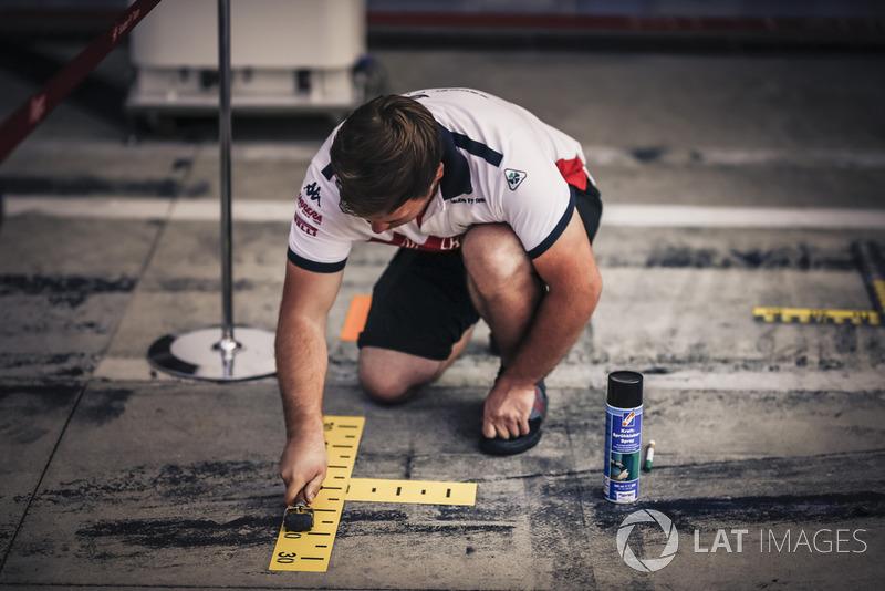 Un mécanicien Sauber prépare l'emplacement aux stands