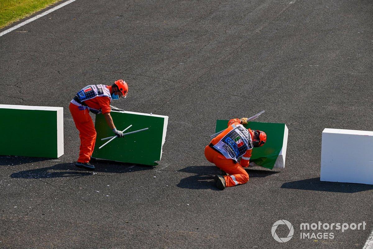 Los oficiales de pista reparan la barrera rota después de que Sebastian Vettel, el Ferrari SF1000 chocó con ella