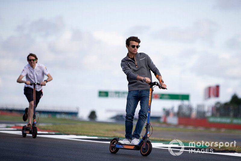 Lando Norris, McLaren walks the track on a scooter