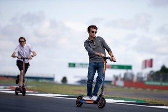 Lando Norris, McLaren walks the track on a scooter