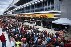 Fans in the pit lane walk outside of the AMG Mercedes garage