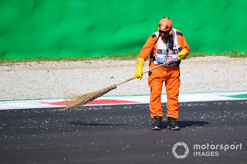 Marshal sweeps the track with a brush