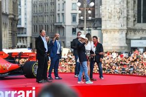 Gerhard Berger, Alain Prost, and Ivan Capelli on stage as Arturo Merzario waves in front of them