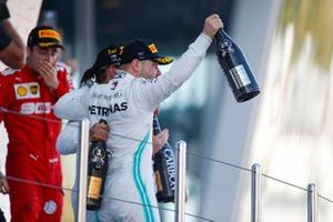 Winner Lewis Hamilton, Mercedes AMG F1, and Valtteri Bottas, Mercedes AMG F1, spray champagne on the podium. Charles Leclerc, Ferrari, looks on