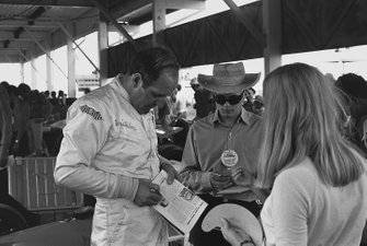 Dennis Hulme, McLaren M14A-Ford signs autographs in the pits