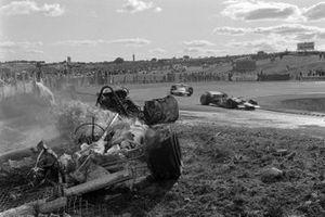Graham Hill, Lotus 49C Ford, Rolf Stommelen, Brabham BT33 Ford, pasan un un coche en llamas