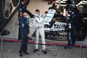 Daniil Kvyat, AlphaTauri, stands in the pit lane, in front of the team's garage