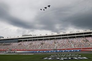Military aircraft perform a flyover empty stands before the race