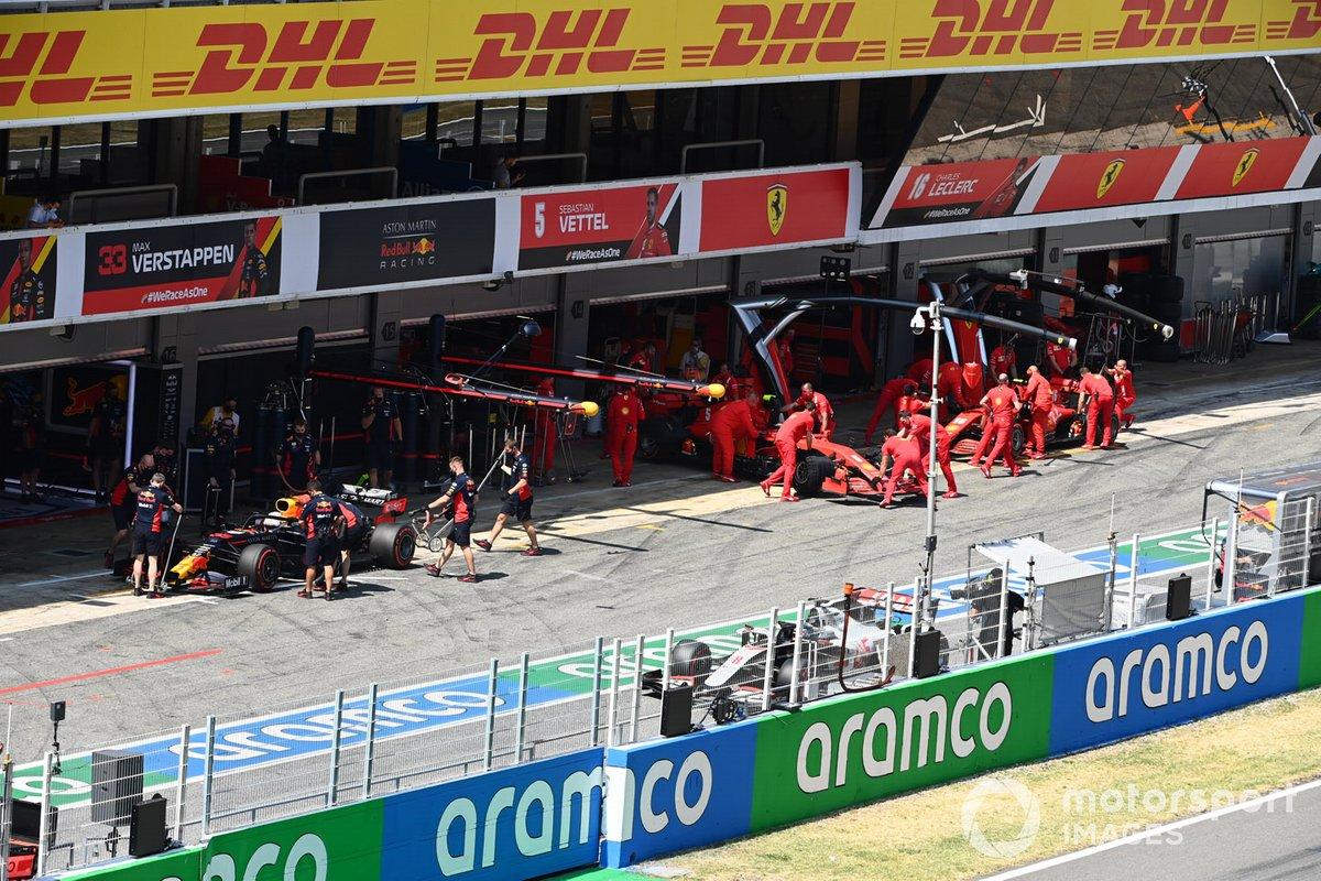 Max Verstappen, Red Bull Racing RB16, en el pit lane mientras Charles Leclerc, Ferrari SF1000, es devuelto al garaje