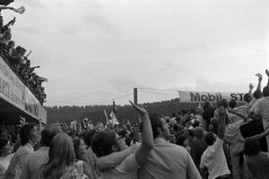 Fans wave to the television helicopter flying around the track