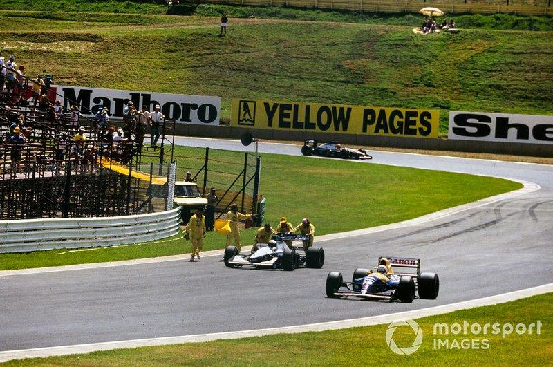 Nigel Mansell, Williams FW14B Renault, pasa por delante de los comisarios que cuidan el coche de Giovanna Amati, Brabham BT60B