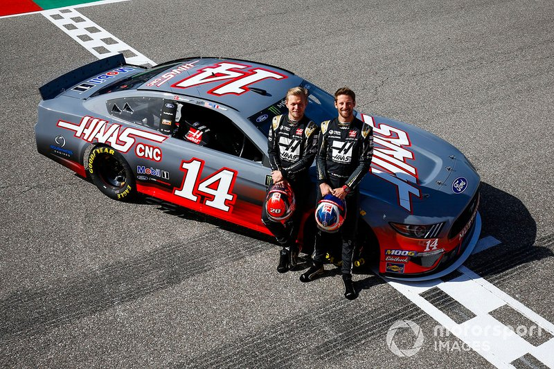 Kevin Magnussen, Haas F1 Team Team, and Romain Grosjean, Haas F1 Team Team, pose with a NASCAR