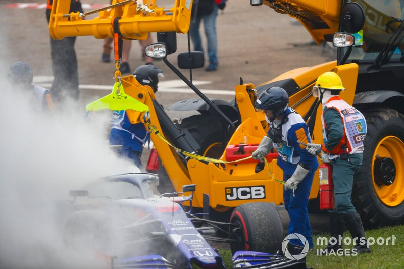 Marshals assist the smoking car of Daniil Kvyat