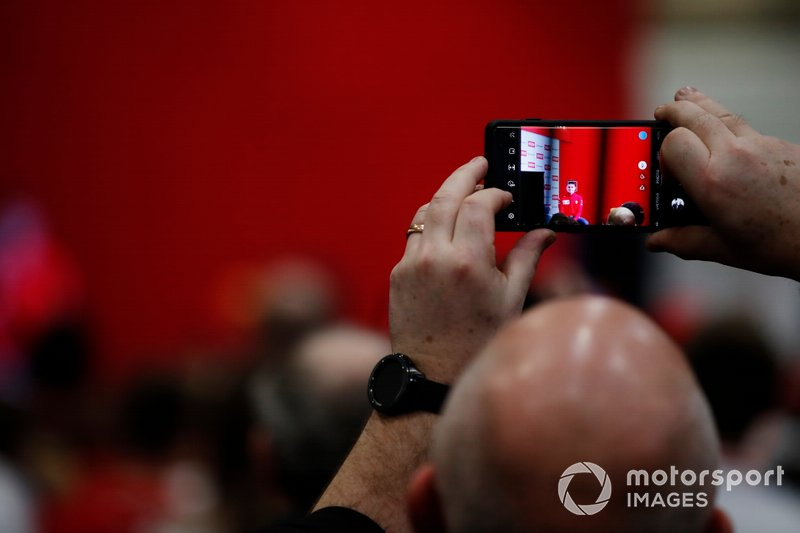 A fan takes a photograph of Charles Leclerc being interviewed on the Autosport stage
