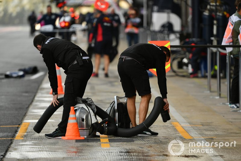 Mercedes mechanics try to dry their pitbox