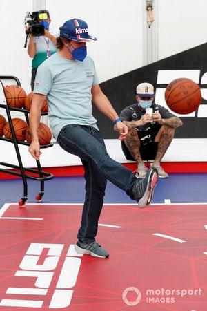 Fernando Alonso, Alpine F1, kicks a basketball