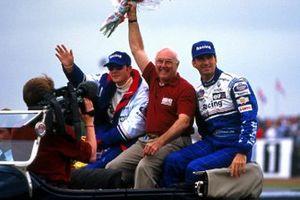 Murray Walker, Commentateur pour la BBC salue la foule. À ses côtés les pilotes Rothmans Williams Damon Hill et Jacques Villeneuve