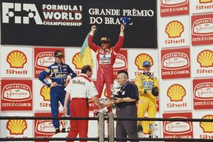 Ayrton Senna, McLaren, celebrates victory on the podium alongside second placed Damon Hill, Williams, and third placed Michael Schumacher, Benetton, as Juan Manuel Fangio presents the constructors trophy to Ron Dennis
