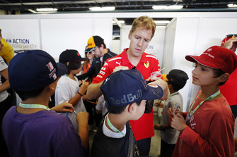 A young fan has a cap signed by Sebastian Vettel, Ferrari.