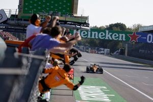 The McLaren team cheer from the pit wall as Lando Norris, McLaren MCL35M, 2nd position, completes a McLaren clean sweep