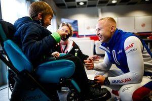 Nikita Mazepin, Haas F1, spreekt met een jonge gast in de garage