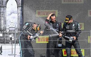 Lewis Hamilton, Mercedes, 1st position, Valtteri Bottas, Mercedes, 3rd position, and the Mercedes trophy delegate celebrate with Champagne on the podium