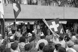 Fans waving Swiss flags in the pit lane after Jo Siffert's victory