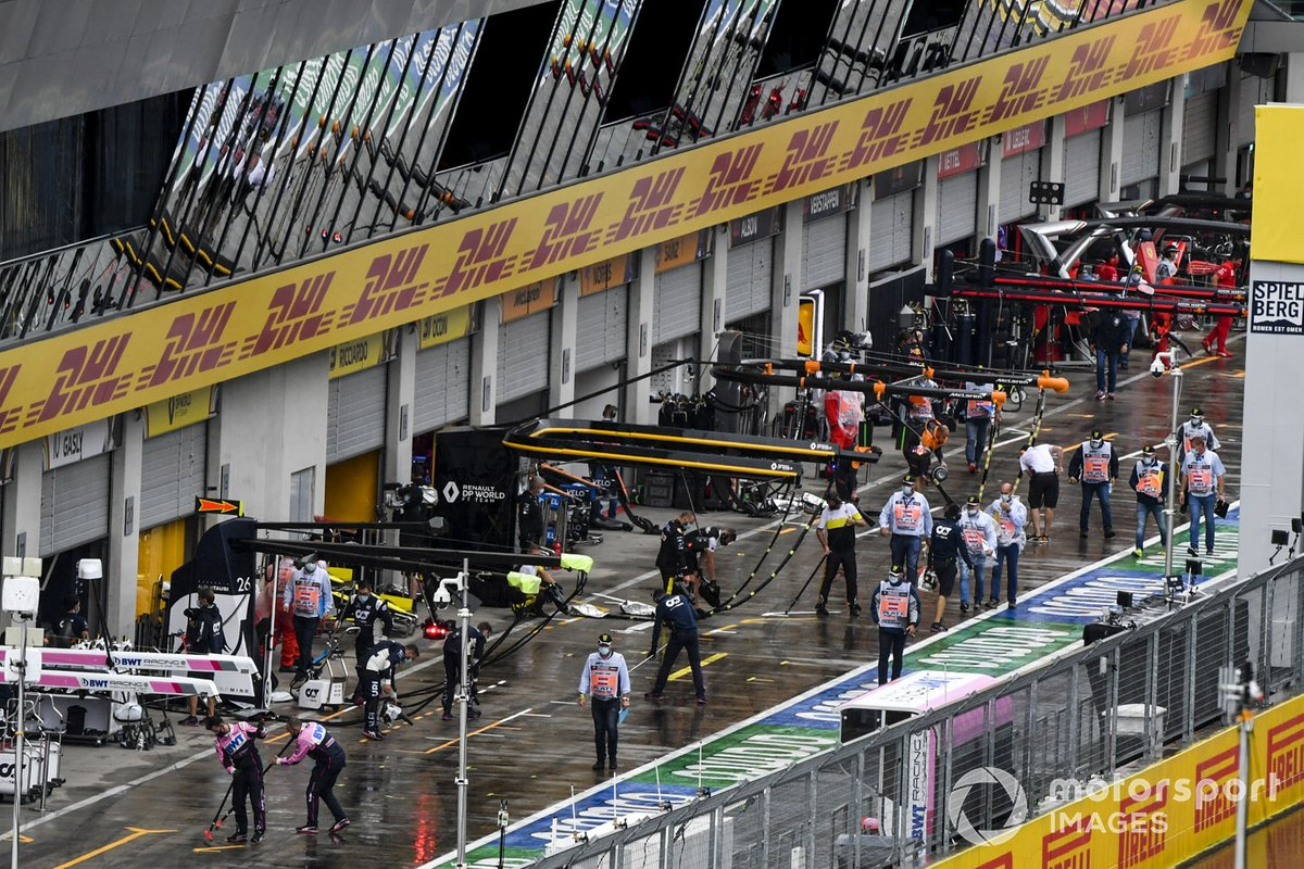Mechanics sweep water away from the pit lane