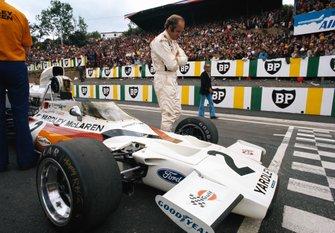 Denny Hulme aux côtés de sa McLaren M19C Ford sur la grille